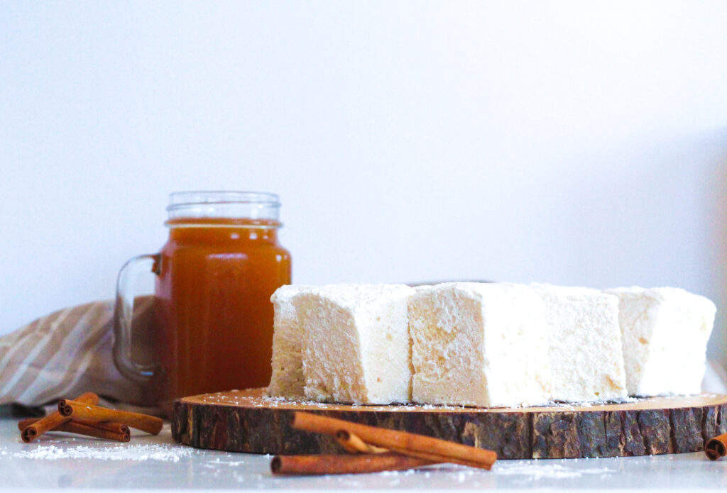 Apple cider marshmallows on a round wooden surface in front of a glass of apple cider surrounded by cinnamon sticks