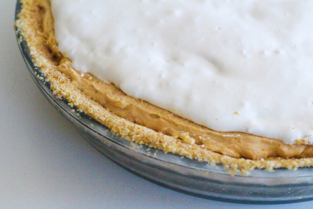 Close up of the layers of a fluffernutter pie - bread crumb crust, peanut butter pie filling, marshmallow fluff topping